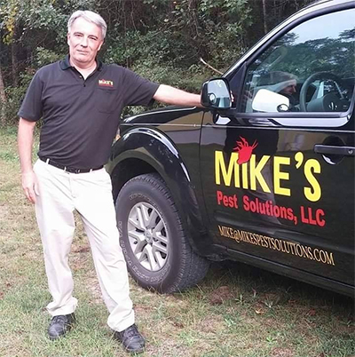 Mike standing next to a Mike's Pest Solutions vehicle